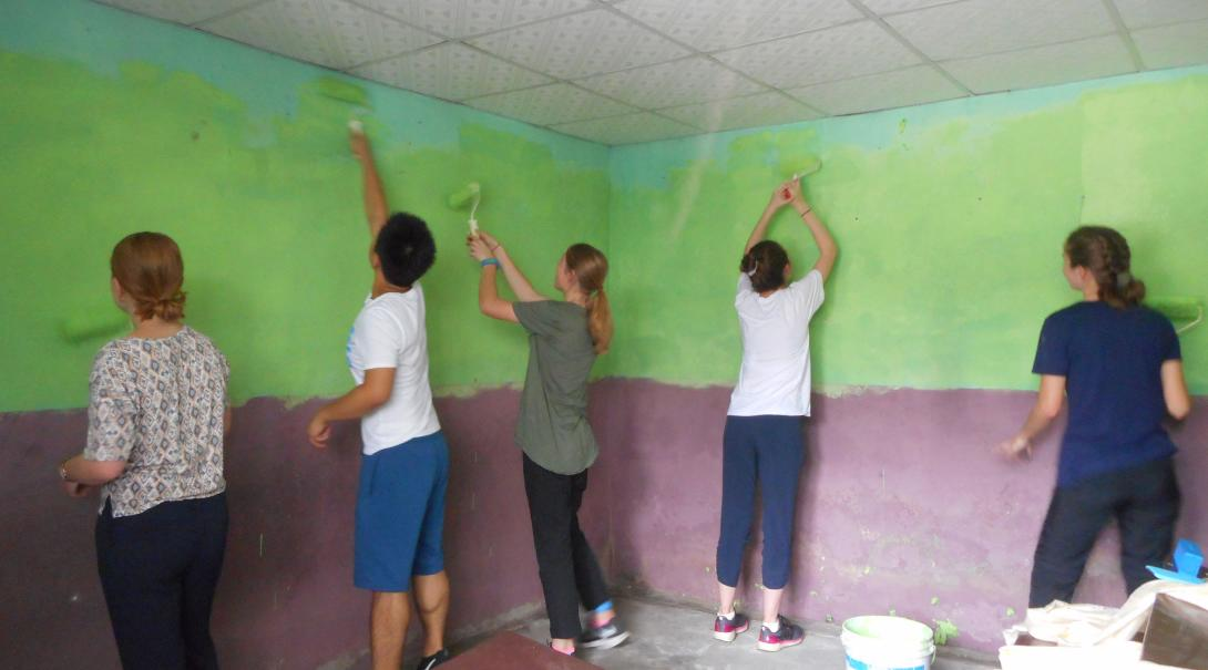 High School Special volunteers painting the walls of a classroom in Nepal